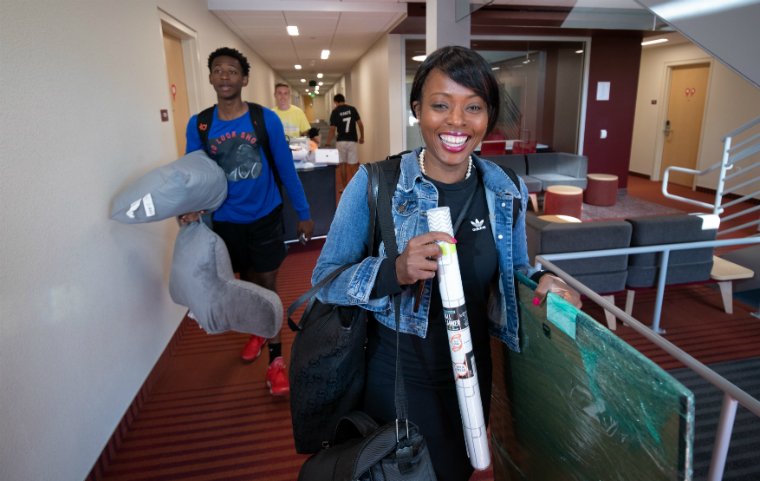 Two students smiling holding belongings as they move into Finn Hall